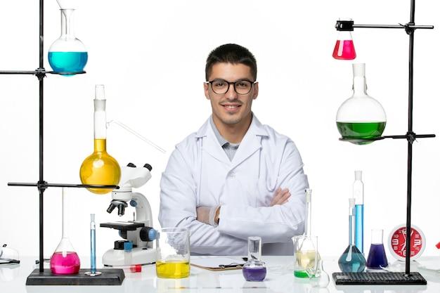 解決策と一緒に座って、白い背景のウイルスcovid-病気科学に微笑んでいる医療スーツの正面図男性化学者