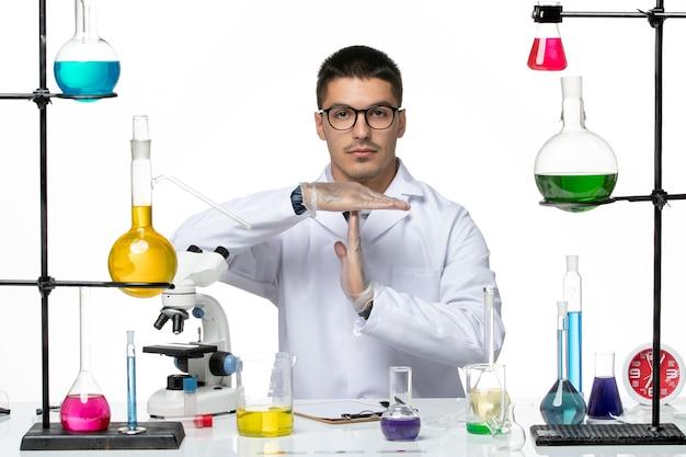 白い背景のウイルスcovid病科学のソリューションと一緒に座っている医療スーツの正面図男性化学者
