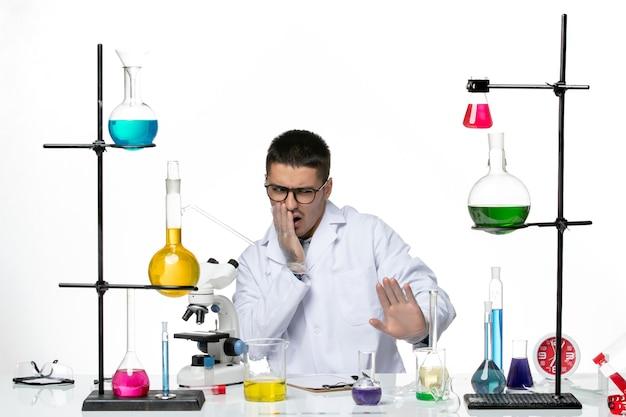 Вид спереди мужского химика в медицинском костюме, сидящего с растворами на белом столе
