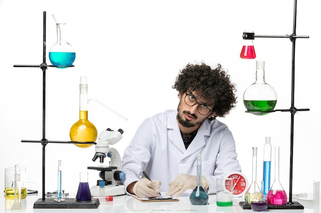 空白にメモを書き留める医療スーツの正面図男性化学者