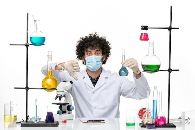 흰색 의료 양복과 마스크 공백에 파란색 솔루션을 들고 전면보기 남성 화학자