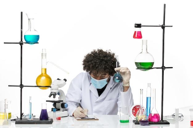 白い医療スーツと白いスペースに書き込みソリューションを保持しているマスクを持つ男性化学者の正面図