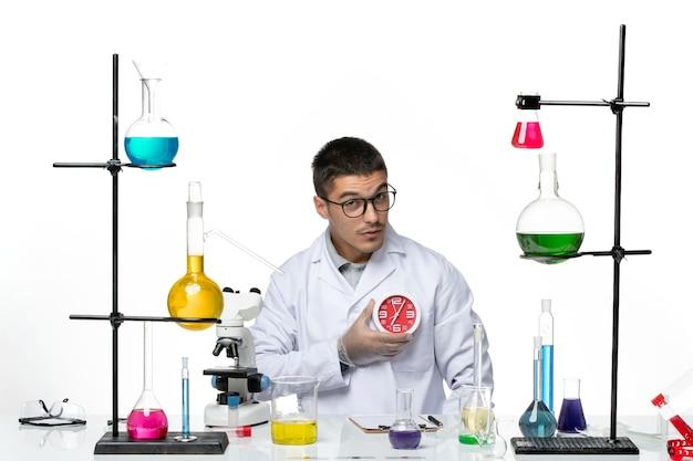 明るい白の背景に時計を保持している白い医療スーツの正面図男性化学者ウイルス病科学研究所covid