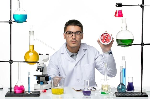 白い背景に時計を保持している白い医療スーツの正面図男性化学者covid-病気ウイルス科学研究室