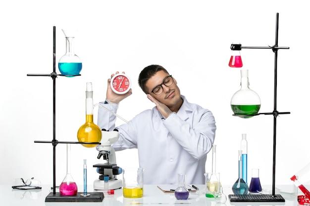 Вид спереди мужской химик в белом медицинском костюме с часами на светлом белом столе вирусная болезнь научная лаборатория covid