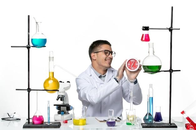 Вид спереди мужской химик в белом медицинском костюме с часами на белом столе, научная лаборатория по вирусным заболеваниям