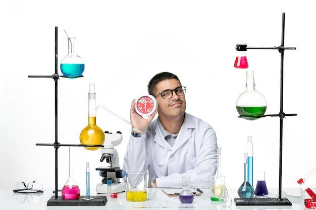 Вид спереди мужской химик в белом медицинском костюме с часами на белом столе вирусная болезнь научная лаборатория covid