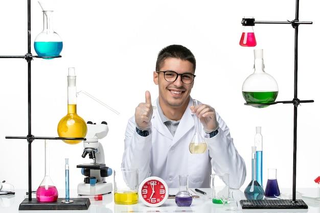 溶液とフラスコを保持し、白い背景に笑みを浮かべて白い医療スーツの正面図男性化学者ウイルス科学研究所のパンデミック