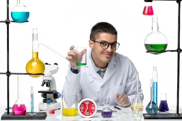 白い背景のウイルス科学共同パンデミックラボで溶液とフラスコを保持している白い医療スーツの正面図男性化学者