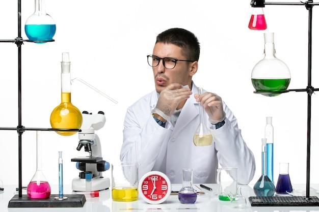 白い背景のウイルス科学研究所のパンデミックに解決策とフラスコを保持している白い医療スーツの正面図男性化学者