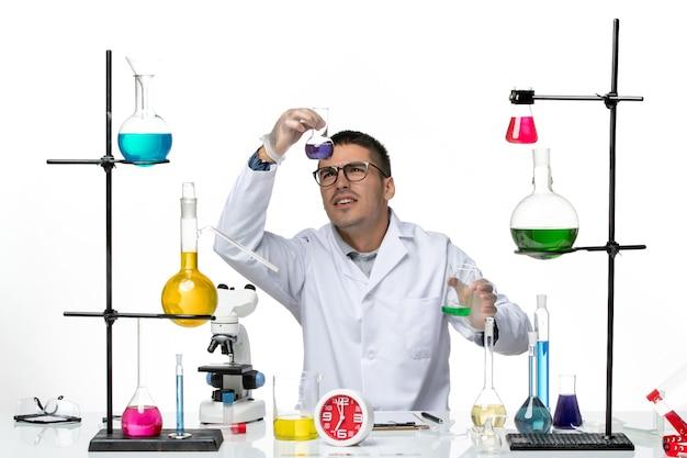 Вид спереди мужской химик в белом медицинском костюме, держащий колбы с растворами на белом столе, вирусная наука, пандемическая лаборатория covid