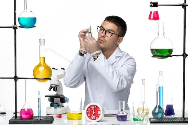 白い背景に注射を保持している白い医療スーツの正面図男性化学者ウイルス科学共同パンデミックラボ