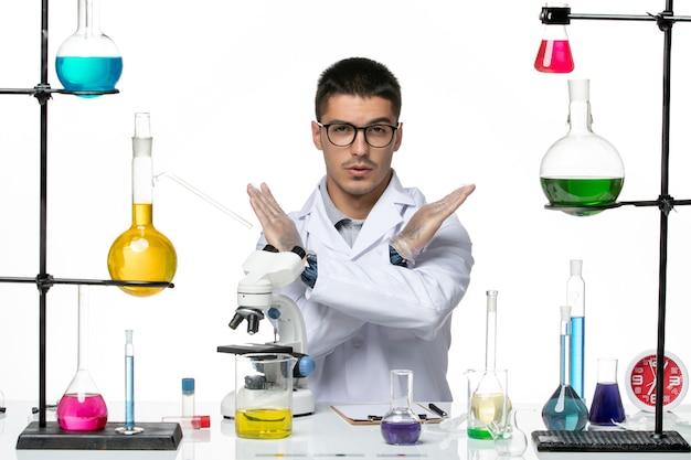 白い背景のウイルス研究所covid-病気科学の禁止サインを示す白い医療スーツの正面図男性化学者