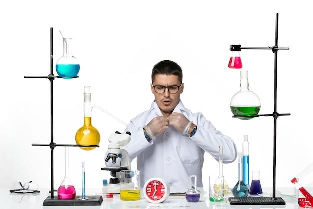 Вид спереди мужчина-химик в белом медицинском костюме сидит и готовится к работе на белом столе вирусная наука covid- пандемическая лаборатория