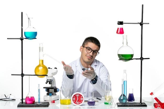 Вид спереди мужского химика в белом медицинском костюме, сидящего с разными растворами на белом столе, вирусная лаборатория, научная лаборатория covid