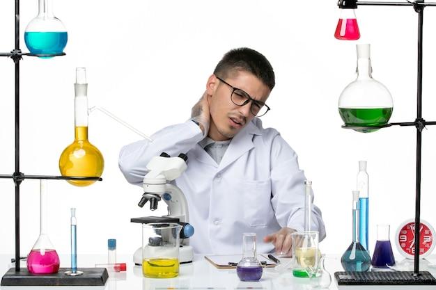 白い背景に痛みを伴う解決策と一緒に座っている白い医療スーツの正面図男性化学者ウイルスラボcovid-diseasescience