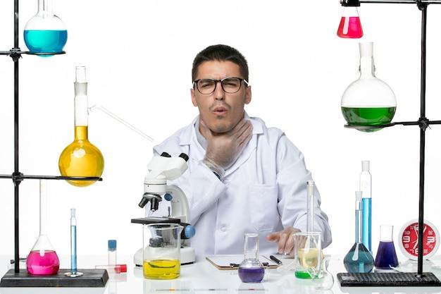 白い背景に喉の痛みがあるソリューションと一緒に座っている白い医療スーツの正面図男性化学者ウイルスラボcovid-diseasescience