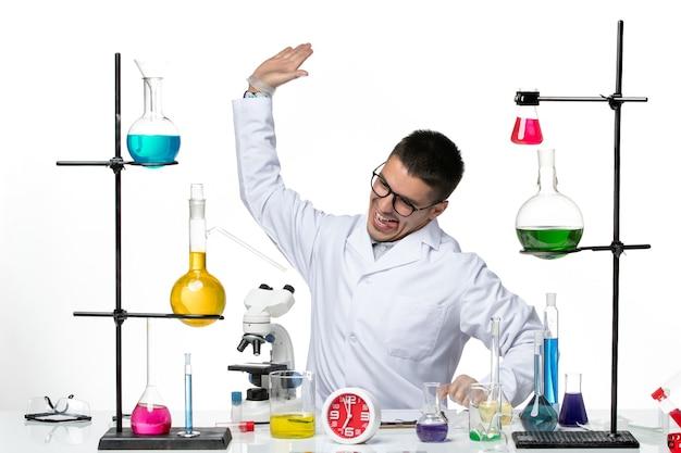 밝은 흰색 배경에 솔루션과 함께 앉아 흰색 의료 소송에서 전면보기 남성 화학자 바이러스 과학 covid 전염병 연구소