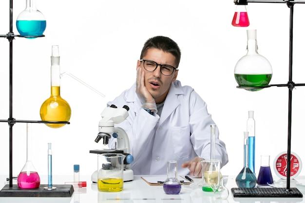 白い背景のウイルスラボcovid病科学のソリューションと一緒に座っている白い医療スーツの正面図男性化学者