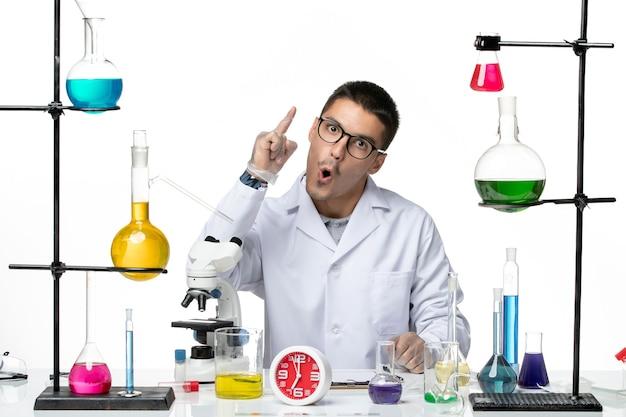 白い背景のウイルス科学covidパンデミックラボでソリューションと一緒に座っている白い医療スーツの正面図男性化学者