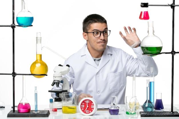 Вид спереди мужской химик в белом медицинском костюме, сидящий с растворами на белом столе, вирусная наука, пандемическая лаборатория covid