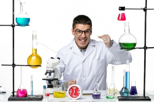 明るい白の背景にソリューションと座っている白い医療スーツの正面図男性化学者ウイルス科学covidパンデミックラボ