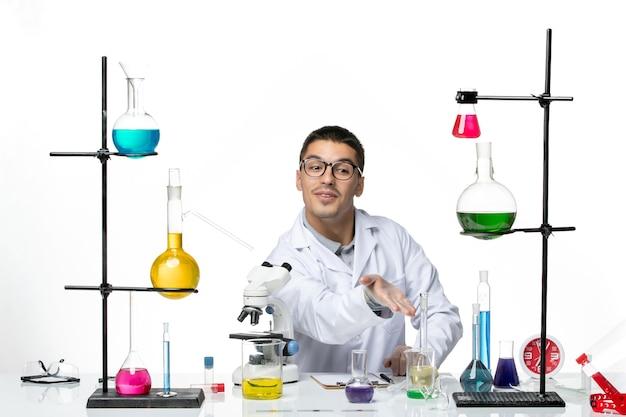 Вид спереди мужской химик в белом медицинском костюме, сидящий с растворами на белом фоне, вирусная лаборатория, наука о заболевании ковидом