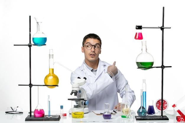 Вид спереди мужского химика в белом медицинском костюме, сидящего с растворами на белом столе, вирусная лаборатория, наука о заболевании ковидом