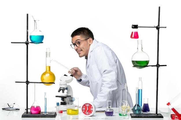 Вид спереди мужской химик в белом медицинском костюме пытается спрятаться на белом фоне вирусная наука covid- пандемическая лаборатория