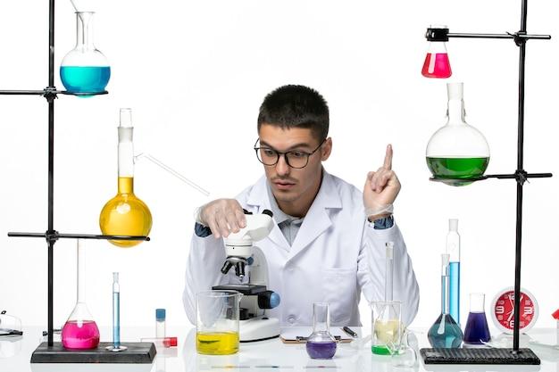 白い背景のウイルスcovid-diseaseラボ科学の顕微鏡を使用して白い医療スーツの正面図男性化学者
