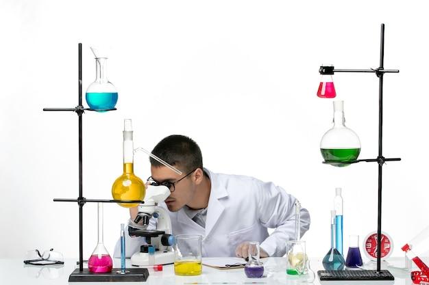 Вид спереди мужской химик в белом медицинском костюме с помощью микроскопа на белом фоне вирус covid- болезнь науки
