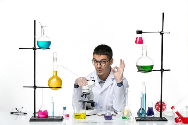 밝은 흰색 배경에 현미경을 사용하여 흰색 의료 소송에서 전면보기 남성 화학자 바이러스 covid- 질병 실험실 과학