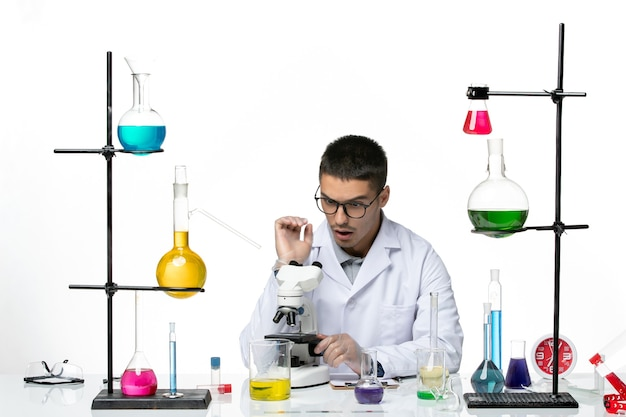 밝은 흰색 배경에 현미경을 사용하여 흰색 의료 소송에서 전면보기 남성 화학자 바이러스 covid- 질병 과학