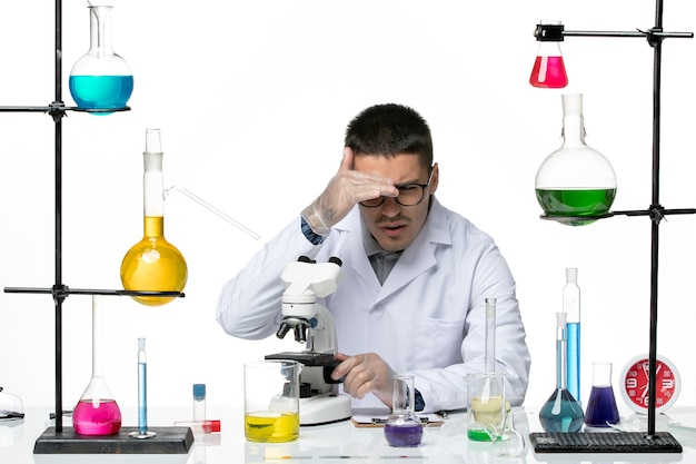 Химик-мужчина в белом медицинском костюме, вид спереди, с помощью микроскопа на белом столе, вирусная наука о коронавирусе