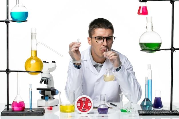 明るい白の背景でさまざまなソリューションを使用して作業している白い医療スーツの正面図男性化学者ウイルス科学研究所covidパンデミック