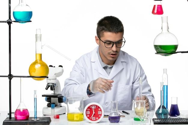 白い背景のウイルス科学研究所covidパンデミックでさまざまなソリューションを使用して作業している白い医療スーツの正面図男性化学者