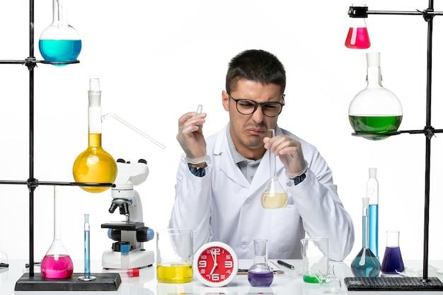 ホワイトデスクウイルス科学研究所のコビッドパンデミックでさまざまなソリューションを扱う白い医療スーツの正面図男性化学者