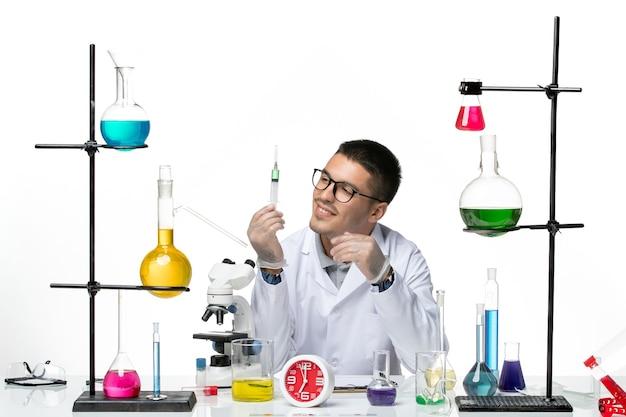白い背景のウイルス科学共同パンデミックラボで注射を使用して作業している白い医療スーツの正面図男性化学者