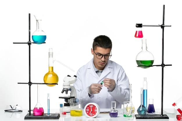 白い背景のウイルス科学のパンデミックで注射を使用して作業している白い医療スーツの正面図男性化学者