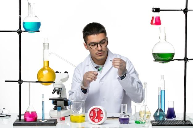 白い背景のウイルス科学共同パンデミックラボでソリューションを使用して作業している白い医療スーツの正面図男性化学者