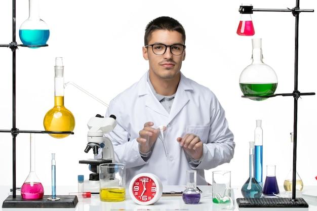 白い背景の科学covid-labパンデミックウイルスのソリューションで作業している白い医療スーツの正面図男性化学者