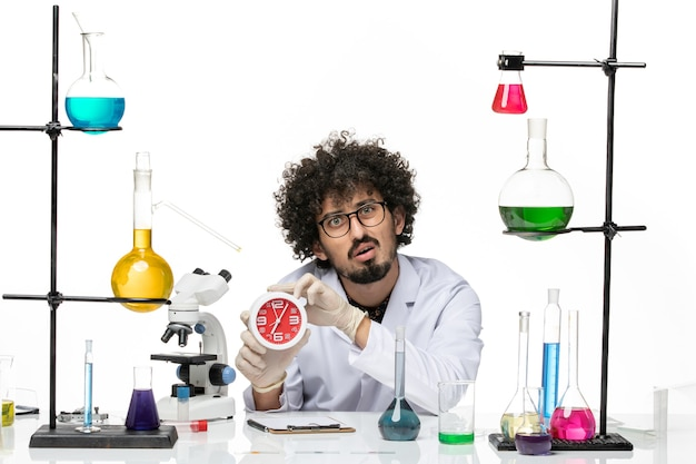 Front view male chemist in medical suit holding clocks on a white space