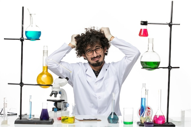 Chimico maschio di vista frontale in vestito medico appena seduto davanti al tavolo con soluzioni che strappano i suoi capelli su uno spazio bianco