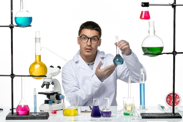 Front view male chemist in medical suit sitting holding solution on white background virus covid- splash disease science