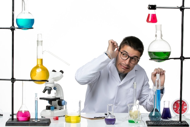 Front view male chemist in medical suit sitting with solutions on white background virus covid- disease science
