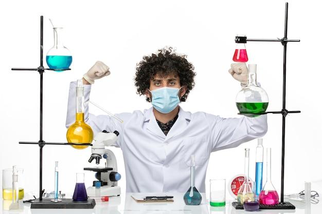 Chimico maschio di vista frontale in vestito medico e con la maschera che si siede appena con le soluzioni che flettono sullo spazio bianco