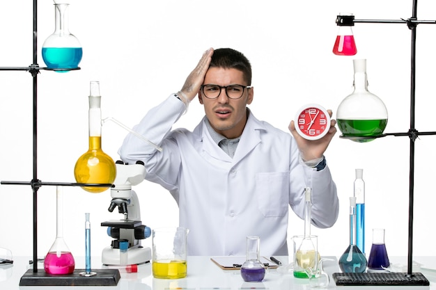 Front view male chemist in white medical suit holding clocks on the white background covid virus disease science lab