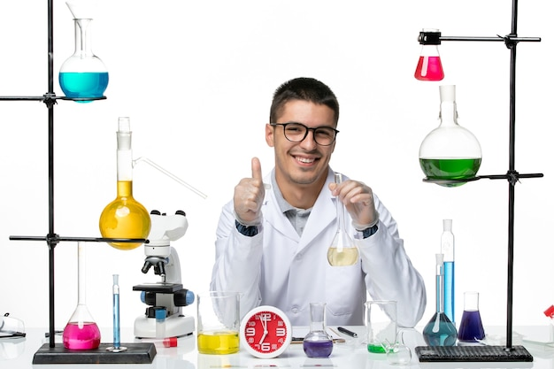 Front view male chemist in white medical suit holding flask with solution and smiling on white background virus science lab covid- pandemic