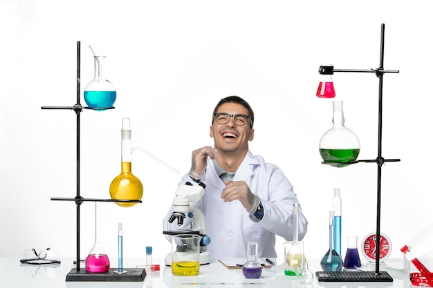Front view male chemist in white medical suit sitting and laughing on white background virus lab covid- disease science