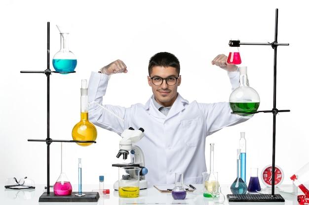 Chimico maschio di vista frontale in vestito medico bianco che si siede con le soluzioni che flettono sul laboratorio di scienza del virus della malattia di covid del fondo bianco